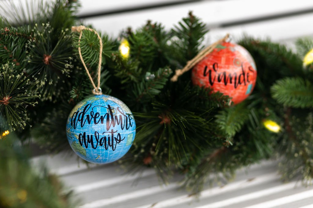 """two world globe ornaments with lettering """"adventure awaits"""" and """"wander"""" hanging from tree branch"""