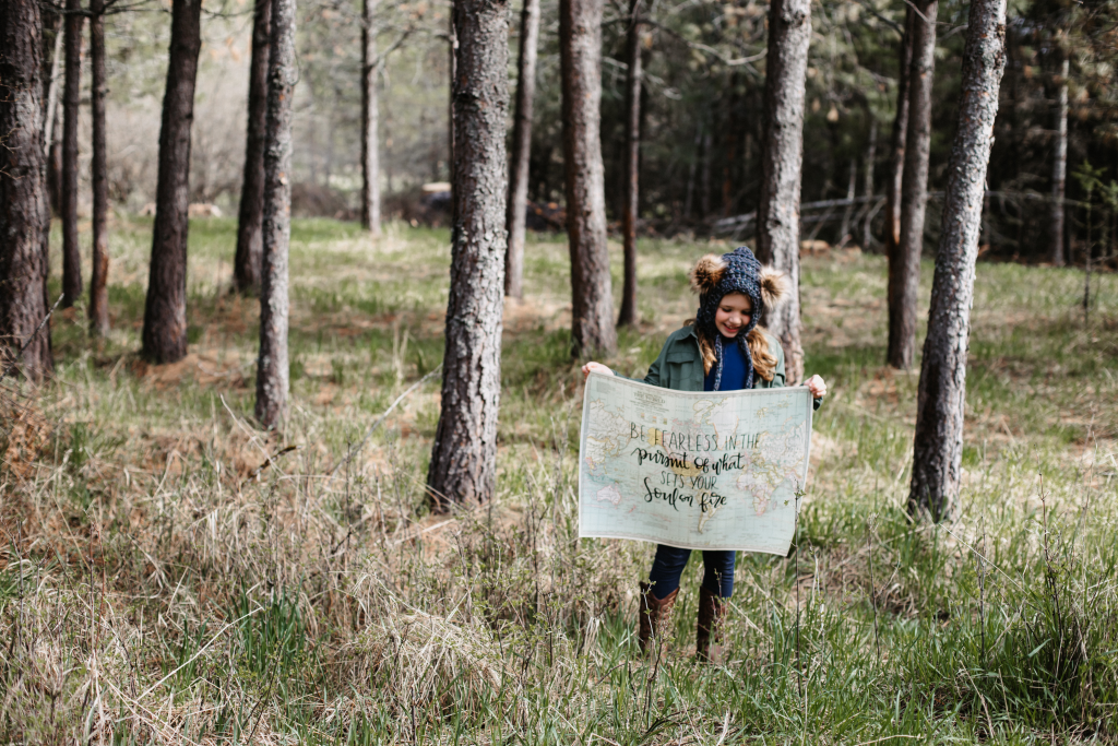 """young girl holding a map in the woods that says """"be fearless in the pursuit of what sets your soul on fire"""""""