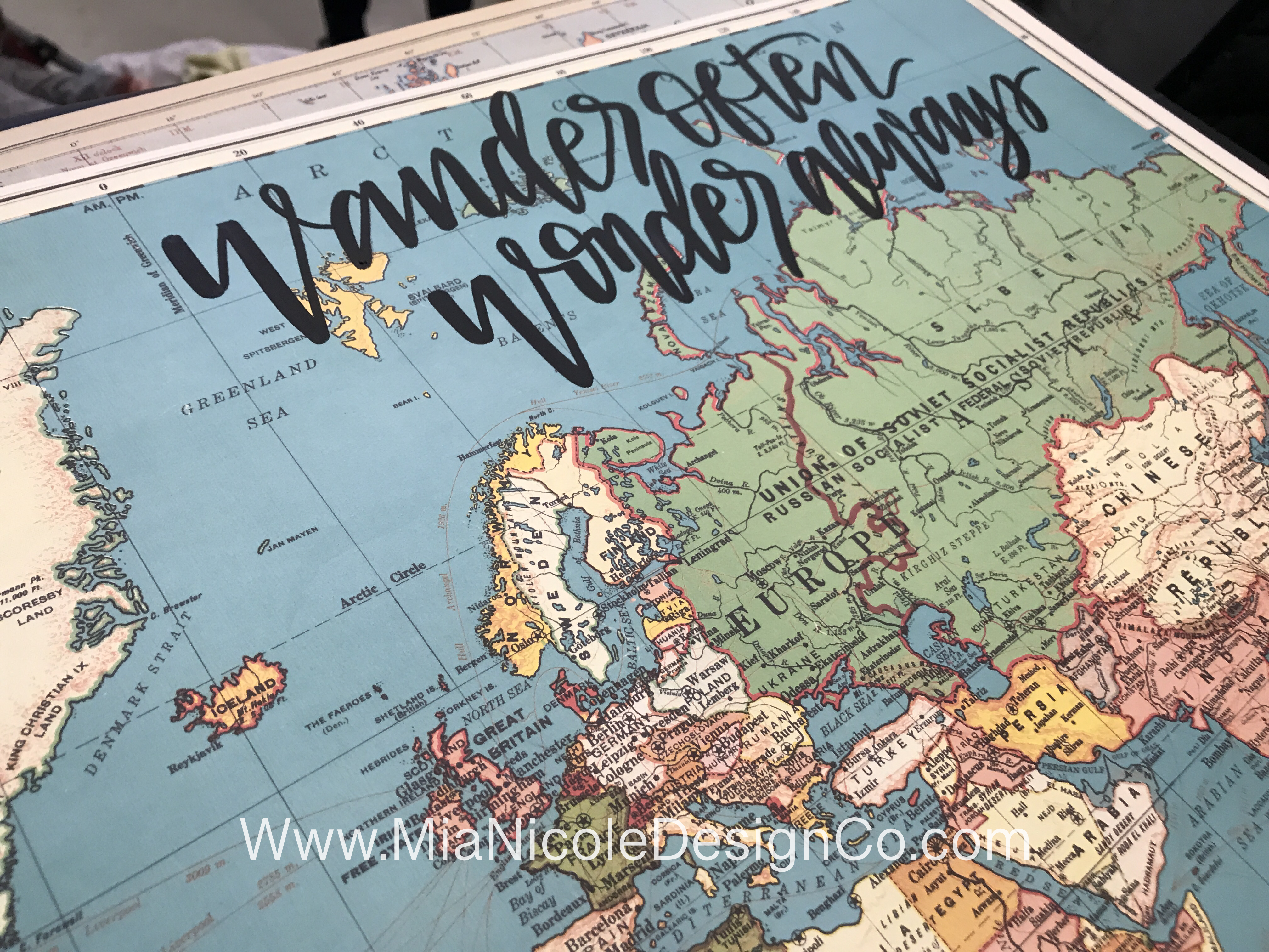 wander often, wonder always hand lettered calligraphy on a world map