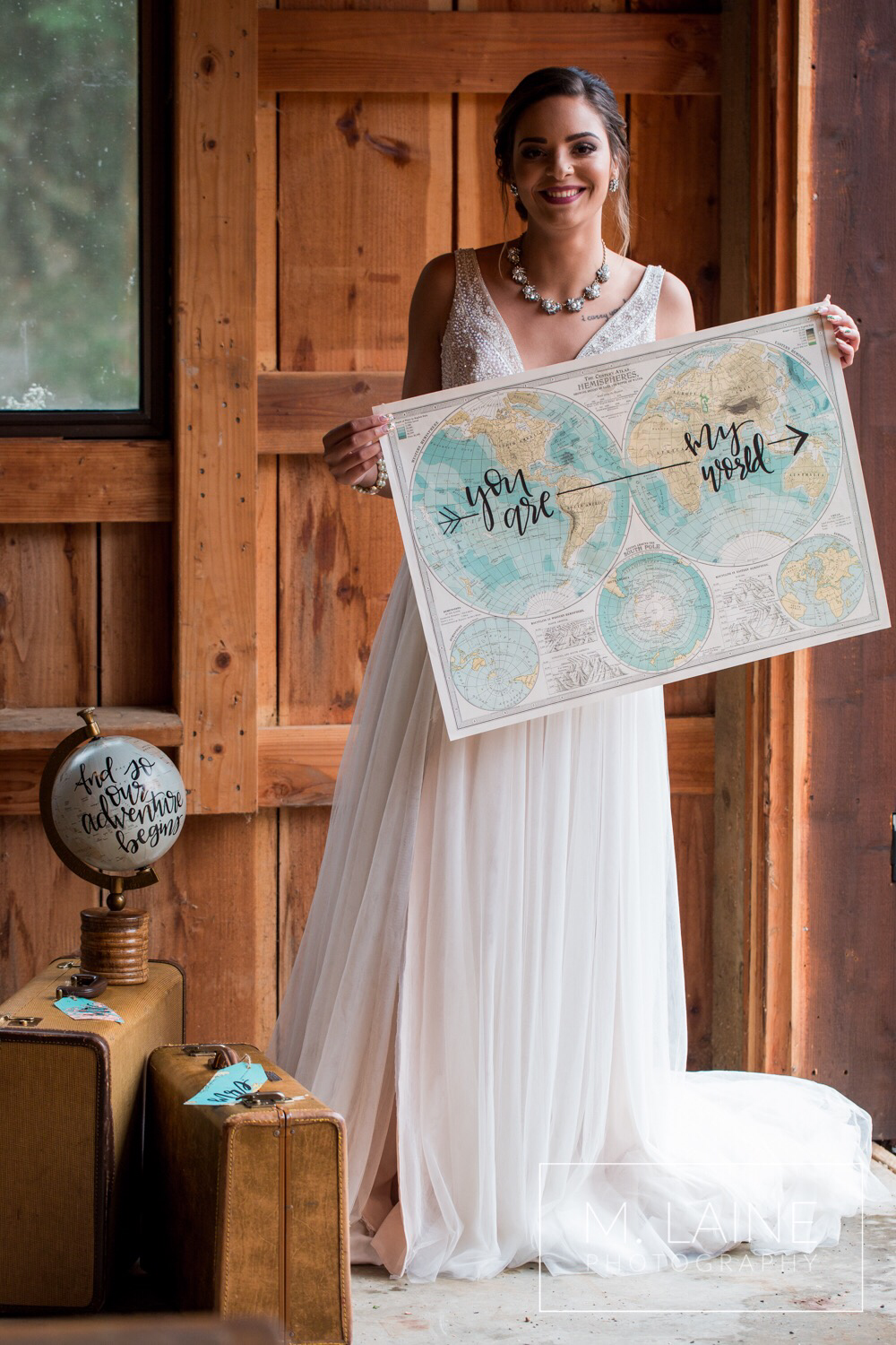 beautiful bride holding up a map that says you are my world.